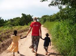 a woman holding hands of 2 children walking down a village road